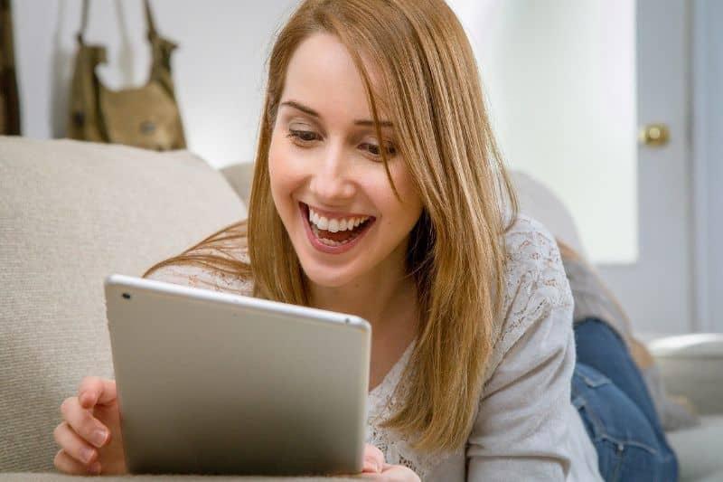 sonriendo mientras usa tablet