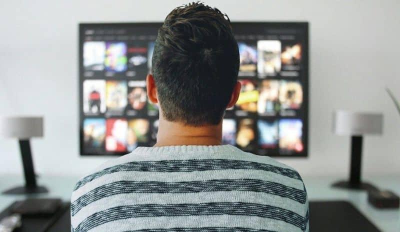 hombre en sala viendo smart tv