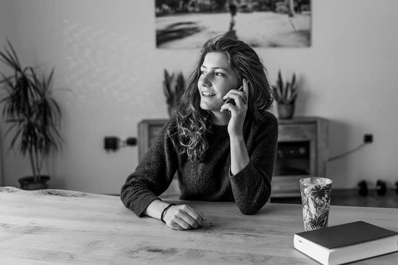 mujer hablando por celular desde su casa